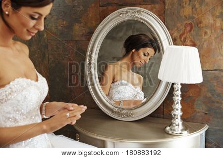 Young bride looking at engagement ring tenderly, sitting front of mirror.