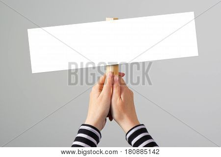 Female hand holding blank mock up banner sign as copy space for quotation text or graphic design