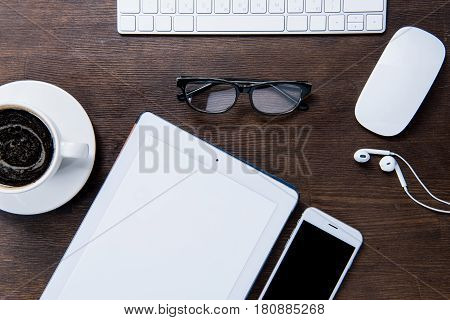 Top View Of Digital Tablet, Cup Of Coffee, Smartphone, Eyeglasses, Computer Mouse And Keyboard At Wo