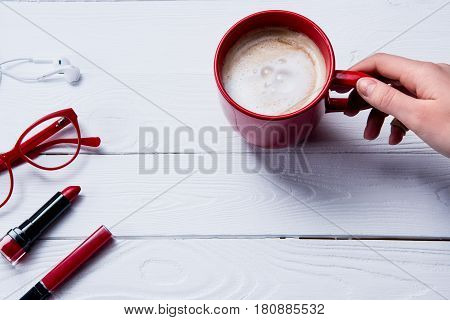top view of hand holding cup of coffee with beauty supplies on table