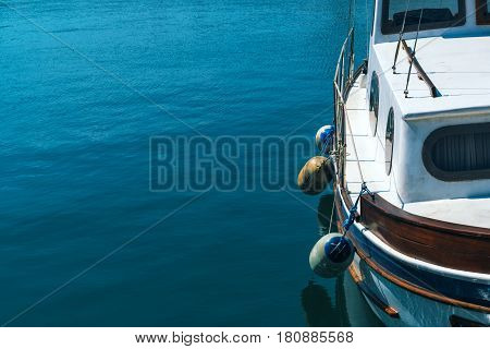 Small fishing boat in harbor with sea water surface as copy space