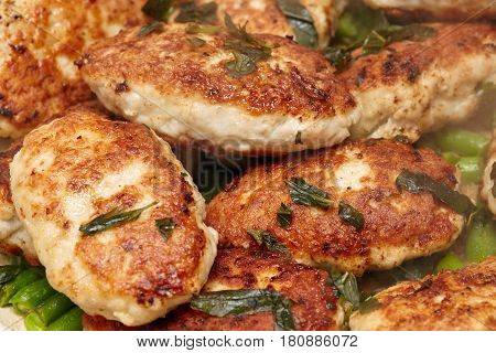 Meat rissoles or cutlets in frying pan cooking process closeup