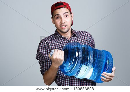 Water delivery. Cheerful young deliveryman holding a water