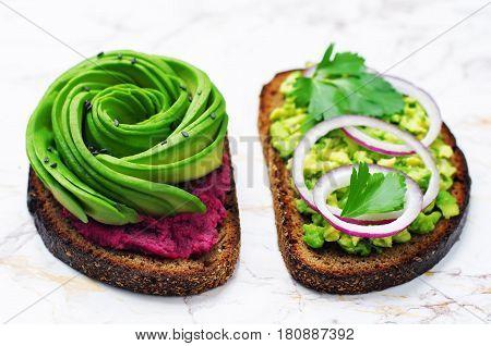 Avocado beet hummus and smashed avocado red onion parsley rye breakfast sandwiches.