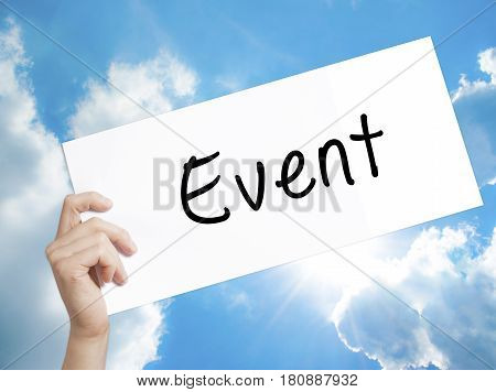 Event Sign on white paper. Man Hand Holding Paper with text. Isolated on sky background. Business concept. Stock Photo