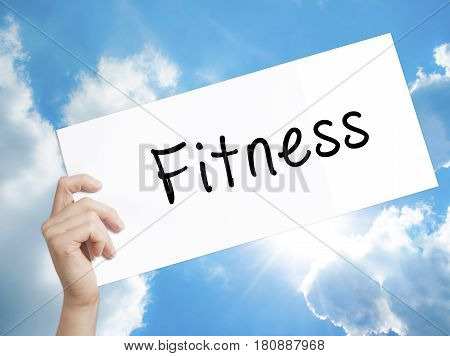Fitness Sign on white paper. Man Hand Holding Paper with text. Isolated on sky background. Business concept. Stock Photo