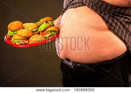 Man belly fat with hamberger group fast food . Breakfast for overweight person. Cropped shot of junk meal leads to obesity. Person regularly overeats concept on black background.