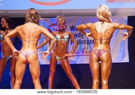 MAASTRICHT THE NETHERLANDS - OCTOBER 25 2015: Female fitness bikini models show their best back pose at championship on stageat the World Grandprix Bodybuilding and Fitness of the WBBF-WFF