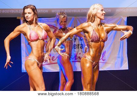 MAASTRICHT THE NETHERLANDS - OCTOBER 25 2015: Female fitness bikini models show their best side pose at championship on stageat the World Grandprix Bodybuilding and Fitness of the WBBF-WFF