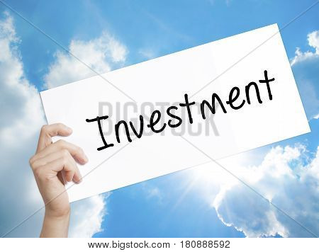 Investment Sign on white paper. Man Hand Holding Paper with text. Isolated on sky background. Business concept. Stock Photo