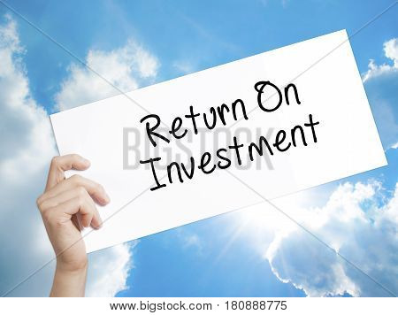 Return On Investment Sign on white paper. Man Hand Holding Paper with text. Isolated on sky background. Business concept. Stock Photo