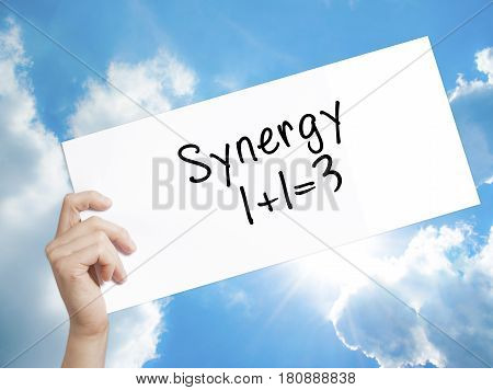 Synergy Concept 1+1=3 Sign On White Paper. Man Hand Holding Paper With Text. Isolated On Sky Backgro