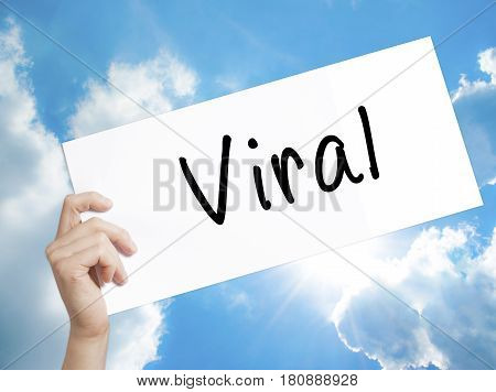 Viral Sign on white paper. Man Hand Holding Paper with text. Isolated on sky background. Business concept. Stock Photo