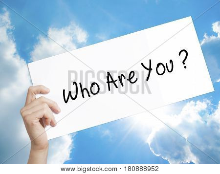 Who Are You Sign on white paper. Man Hand Holding Paper with text. Isolated on sky background. Business concept. Stock Photo
