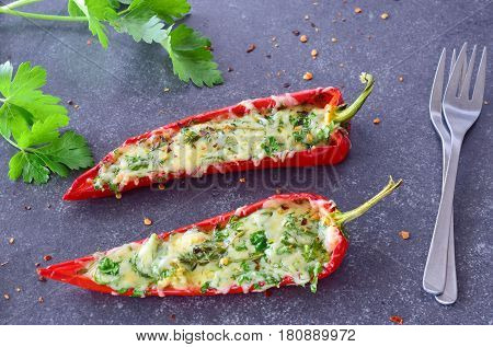 Oven cooked red paprika stuffed with cheese garlic and herbs on an abstract grey background. healthy eating concept. Mediterranean lifestyle.