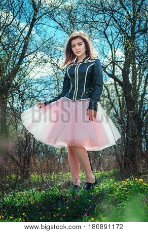 Portrait of beautiful teen girl wearing black leather jacket and pink tutu tulle skirt standing in a spring forest on a green grass with yellow flowers
