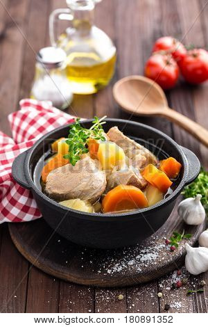 Meat stewed with carrots and potatoes in sauce on wooden rustic background