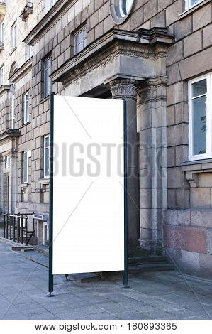 Mock up. Blank outdoor advertising column outdoors, public information board near classical architecture building