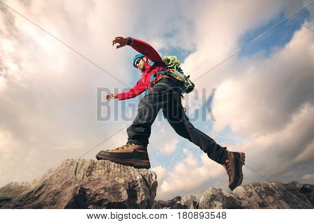 Mountaineer jumps over rocks in mountin, cloudy weather