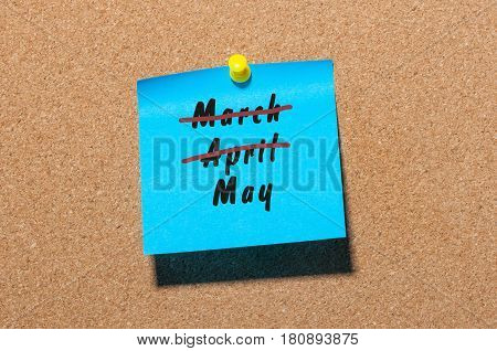 May beginning. Name of month written on blue sticker pinned at noticeboard with crossed out March and April. Spring concept.