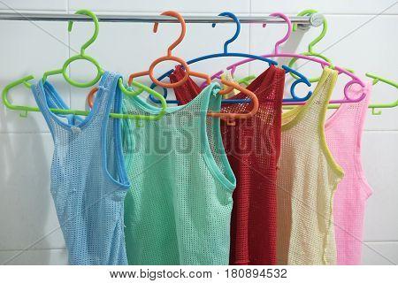 Many colors sleeveless children's shirt on a hanger