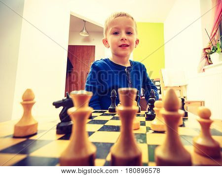 Intelligent smart ass kids games good for brain intelligence concept. Young kid boy playing chess and having fun.