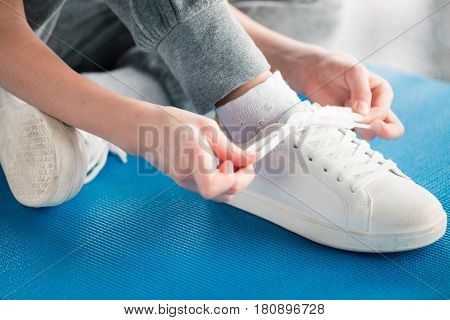 Close-up partial view of girl sitting on yoga mat and tying shoelace