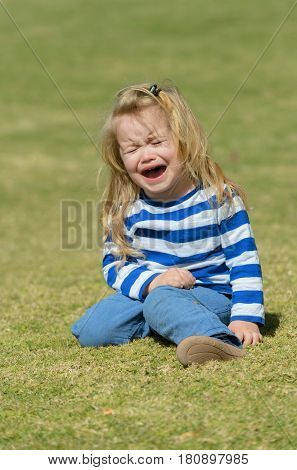 Unhappy Cute Baby Boy Sitting On Green Grass In Park