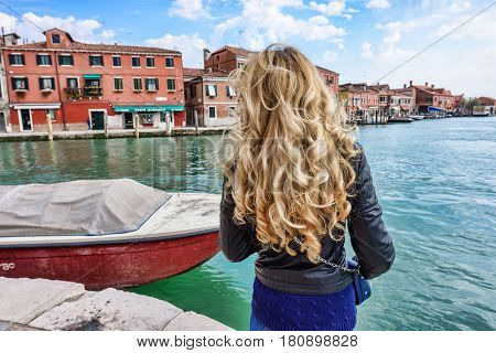 Woman walking in Murano Italy. Traveler or tourist girl exploring the city