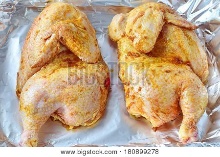 Two halves of raw marinated chicken in a tray on a folio before being roasted. Cooking step by step. Healthy eating concept