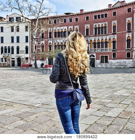 Woman walking in Venice Italy. Traveler or tourist girl exploring the city architecture