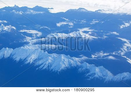 Idyllic snowy mountain peaks or tops under soft white clouds on blue rocky highland environment background. Overcast view from plane flight