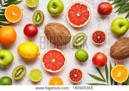Citrus fruits background flat lay, helthy vegetarian organic food, antioxidant detox nutrition diet. Tropical summer assortment mix grapefruit, coconut, orange, apple, mandarin, sliced kiwi fruit
