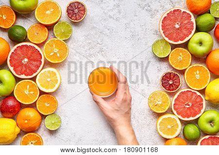 Man's hand holding smoothie or fresh juice in citrus fruits background flat lay, healthy lifestyle vegetarian organic antioxidant detox diet. Tropical summer assortment grapefruit, orange, apple mix
