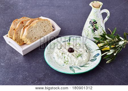 Greek traditional sauce tzatziki with olives, olive oil jar, lemon and bread on a grey abstract background. Healthy eating concept