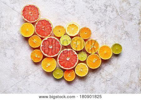 Citrus fruits flat lay on white background table, healthy vegetarian organic food, antioxidant detox diet. Tropical summer assortment mix grapefruit, orange, apple, mandarin, sliced kiwi fruit