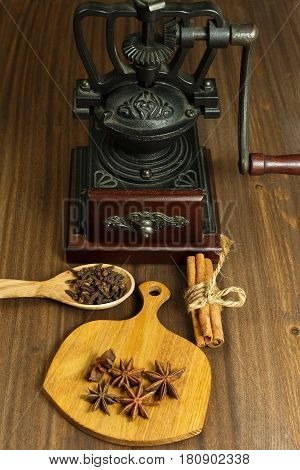 Vintage coffee hand mill and different spices on the tiny cutting board and wooden spoon