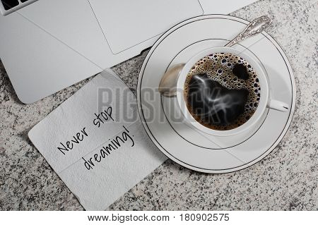 Cup with espresso coffee laptop and a napkin with motivation slogan on table in cafe - top view