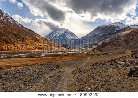 The picturesque autumn landscape with a rocky dirt road winding river mountains covered with snow and golden trees on a background of the sky and clouds