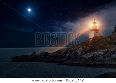 Lighthouse on fjord coast in Norway at night