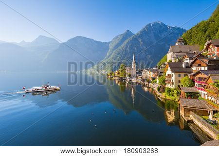 Classic postcard view of famous Hallstatt lakeside town in the Alps with passenger ship in scenic golden morning light on a beautiful sunny day in summer Salzkammergut region Austria