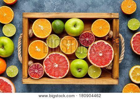 Citrus fruits sliced mix flat lay in wooden tray on blue concrete background, healthy vegetarian organic food, antioxidant detox diet. Tropical summer mix grapefruit, orange, apple, kiwi fruit, lime