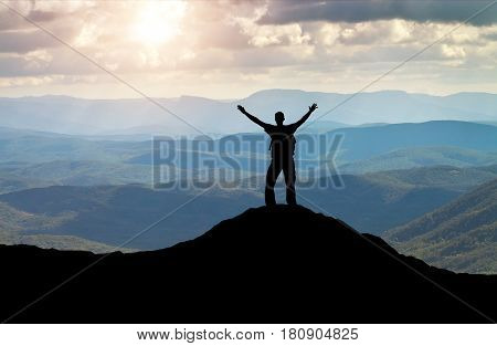 Silhouette of a man on a mountain top. Person on the rock. Sport and active life concept