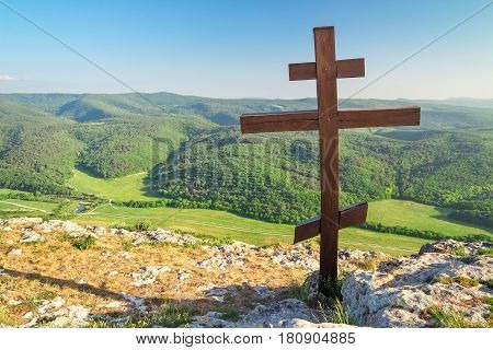 Orthodox cross on top of a mountain. Spring landscape