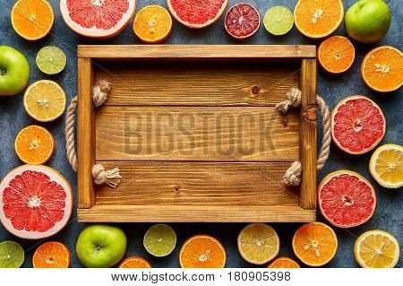 Empty wooden tray box frame, copy blank design space with citrus fruits sliced mix flat lay on blue concrete background, healthy vegetarian organic food, antioxidant detox diet. Tropical summer mix
