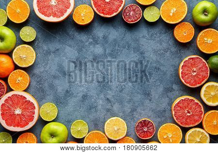 Citrus fruits sliced mix frame flat lay on blue concrete background blank copy design space, healthy vegetarian organic food, antioxidant detox diet. Tropical summer mix grapefruit, orange, apple mix