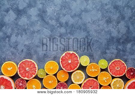 Different citrus fruit on dark grey concrete table. Fruit food background. Healthy eating and diet. Antioxidant, detox, dieting, clean eating, vegetarian, vegan, fitness or healthy lifestyle concept