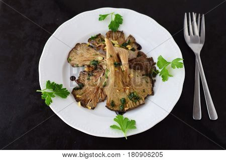Fried Oyster mushrooms with garlic, parsley and balsamic glaze in a white plate on a black abstract background. Healthy concept.