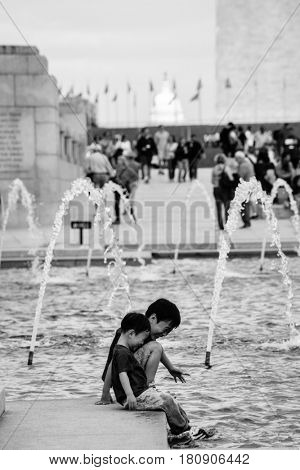 WASHINGTON DC, USA - 03 MAY 2014: The children plays in the pool of World War II Memorial in Washington DC.