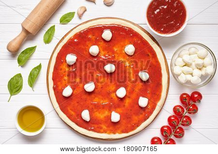 Pizza cooking preparation ingredients. Baking ingredients on the white wooden table: dough, mozzarella, tomatoes sauce, basil, olive oil, tomatoes. Italian food cuisine background pizza margherita